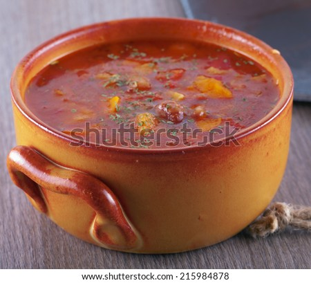 Soup with beans, tomato and bread in crock pot - stock photo