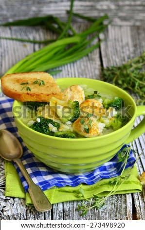 Soup with broccoli,rice and chicken meatball on a wooden table. - stock photo