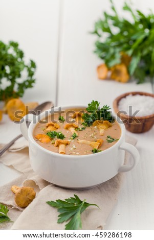 Soup with chanterelles and parsley on white wood