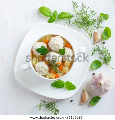 Soup with chicken meatballs and vegetables on white wooden background, top view, square image - stock photo