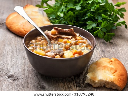 soup with chickpeas and lamb, flat bread, parsley on a wooden background - stock photo