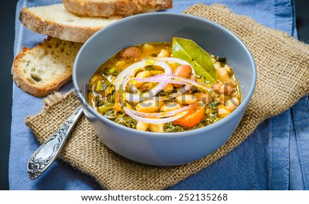 Soup with different vegetables, cannellini beans, cavolo nero, bread.Famous typical tuscan soup, ribollita. Plate with soup. - stock photo
