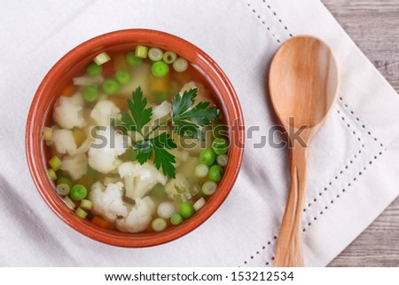 soup with fresh vegetables and greens on wooden background