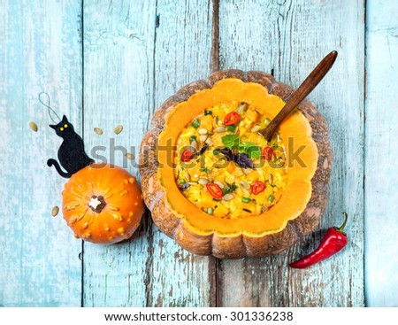 Soup with lentil in the carved pumpkin and black cat toy on the blue wooden background at Halloween party - stock photo