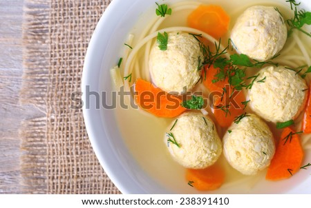 Soup with meatballs and noodles in bowl on wooden background - stock photo