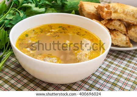 Soup with meatballs and toast with cheese - stock photo