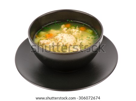 Soup with meatballs in the black bowl  isolated. - stock photo