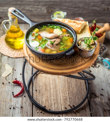 Soup with quail meat, with quail eggs and vegetables, in a frying pan