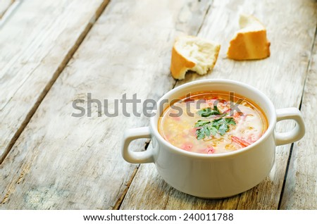 soup with salmon, potatoes and millet on a light woody background. tinting. selective focus - stock photo