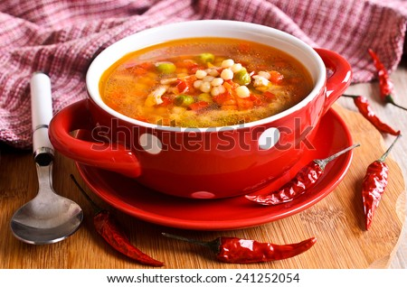 Soup with small pasta and vegetables in a ceramic bowl on a wooden surface - stock photo