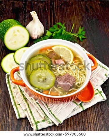 Soup with zucchini, beef, ham, lemon and noodles in a bowl, parsley and dill on a napkin against a dark wooden board
