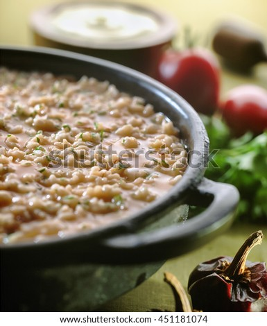 Soupy rice in earthenware casserole - stock photo