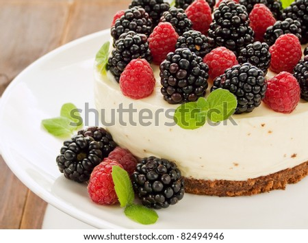 Sour cream cheesecake with raspberries and blackberries. Shallow dof. - stock photo