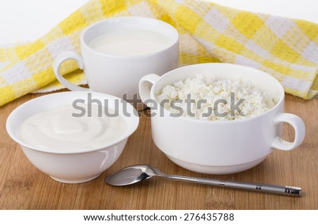 Sour cream, milk and cottage cheese and napkin on bamboo board