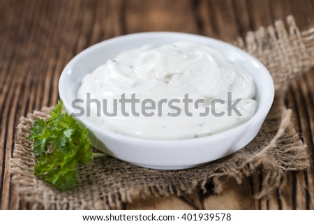 Sour Cream with fresh herbs (close-up shot) on wooden background