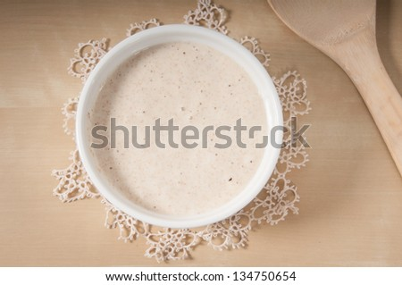 Sourdough in a white bowl on a antique cream doily - stock photo
