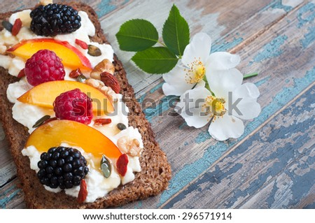 Sourdough rye bread open sandwich with ricotta,nectarine,berries,nuts and seeds with honey drizzle. - stock photo