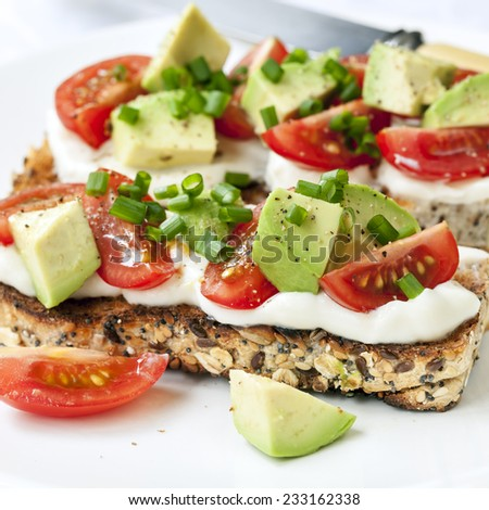 Sourdough toast with avocado, cherry tomatoes, cream cheese and chives. - stock photo