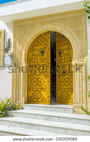 SOUSSE, TUNISIA - AUGUST 28, 2015: The traditional arabic door with the massive stone door frame leads to the old souvenir shop, on August 28 in Sousse.