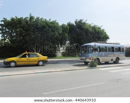 SOUSSE, TUNISIA - SEPTEMBER 13, 2012 : A taxi and a bus driving on the road passing by Port El Kantaoui, the tourist complex near Sousse, Tunisia.