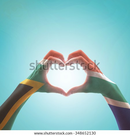 South Africa flag color pattern on woman human hands in heart shape on vintage sky background: Hand sign language symbolic concept of national unity, union, love for the nation and reconciliation  - stock photo
