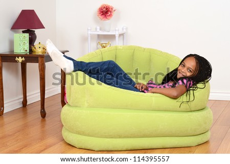 South African child relaxing in green chair