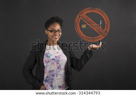 South African or African American black woman teacher or student holding a no smoking sign in her hand standing against a chalk blackboard background inside