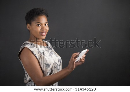 South African or African American black woman teacher or student holding a tablet standing against a chalk blackboard background inside
