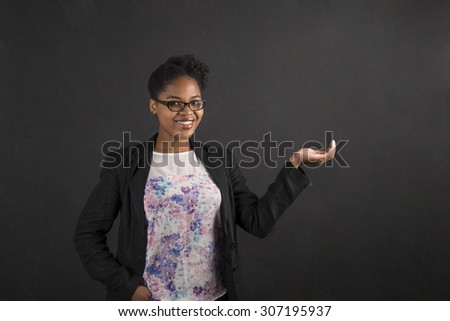 South African or African American black woman teacher or student holding her hand out to the side standing against a chalk blackboard background inside