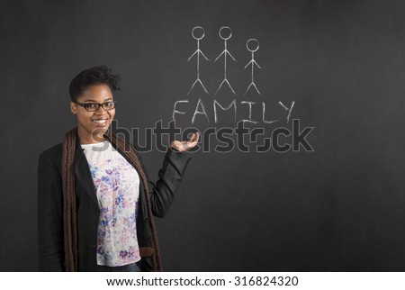 South African or African American black woman teacher or student holding her hand out to the side with a family diagram standing against a chalk blackboard background inside - stock photo
