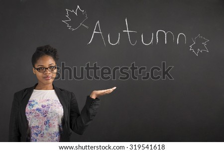 South African or African American black woman teacher or student holding her hand out to the side showing Autumn standing against a chalk blackboard background inside