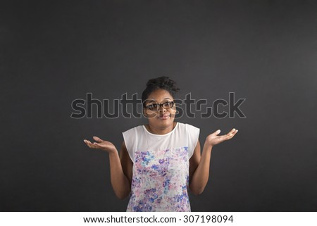 "South African or African American black woman teacher or student posing with an ""I don't know"" gesture on a chalk blackboard background inside"