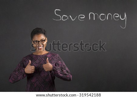 South African or African American black woman teacher or student with a thumbs up hand signal to saving money standing against a chalk blackboard background inside - stock photo