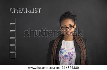 South African or African American black woman teacher or student with her arms behind her back with a checklist on chalk black board background inside - stock photo