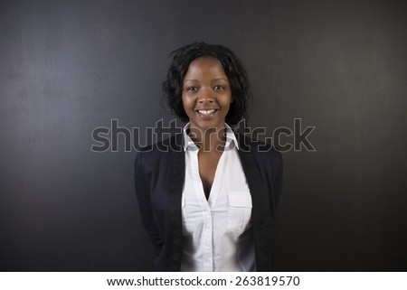South African or African American woman teacher or student against a dark blackboard background - stock photo