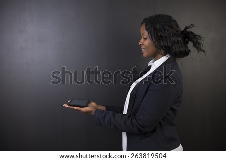 South African or African American woman teacher or student holding computer tablet on blackboard background - stock photo