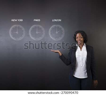 South African or African American woman teacher or student holding hand out displaying the  New York, Paris and London chalk time zone clocks on a blackboard background