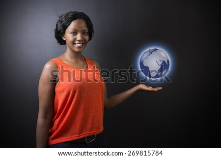South African or African American woman teacher or student holding world earth globe in the palm of her had on black background - stock photo
