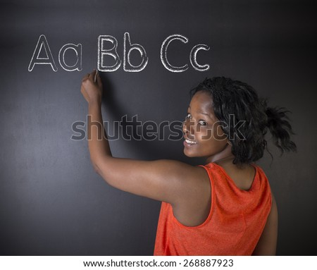 South African or African American woman teacher or student learn alphabet write writing on chalk blackboard background