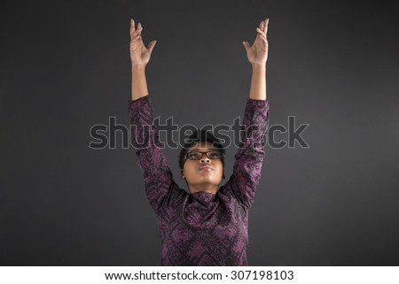 South African or African American woman teacher or student reaching for the sky on blackboard background