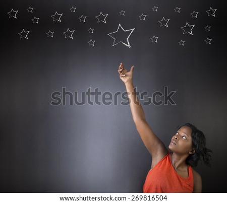 South African or African American woman teacher or student reaching for the stars success against blackboard background - stock photo