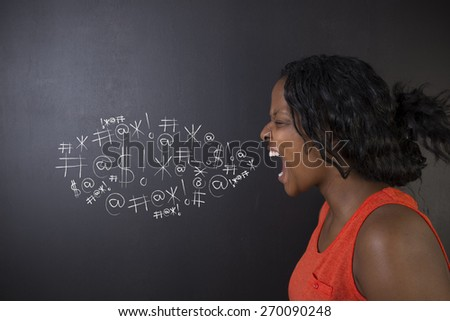 South African or African American woman teacher or student standing against a blackboard background swearing chalk words bubble - stock photo