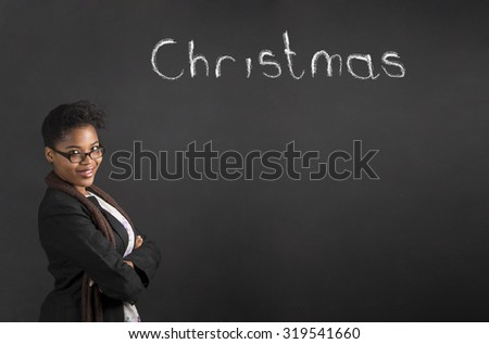 South African or African American woman teacher or student with arms folded thinking about Christmas on chalk black board background - stock photo