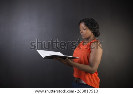 South African or African American woman teacher or student with diary notepad against a blackboard background - stock photo
