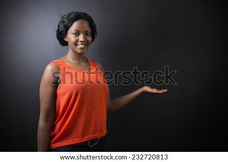 South African or African American woman teacher or student with hand out on chalk black board background