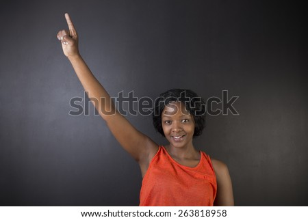 South African or African American woman teacher or student with hand up on chalk black board background - stock photo