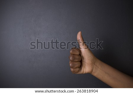 South African or African American woman teacher or student with thumb up on chalk black board background