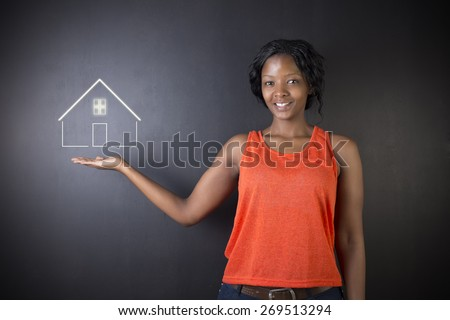 South African or African American woman teacher, student, saleswoman or businesswoman against black background holding house, home or real estate