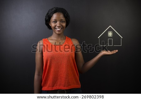 South African or African American woman teacher, student, saleswoman or businesswoman against black background holding house, home or real estate - stock photo
