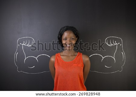 South African or African American woman teacher with healthy strong arm muscles for success on blackboard background - stock photo